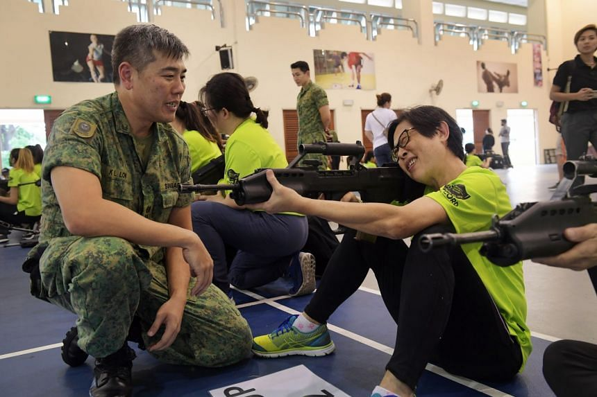 Madam Patsy Chong learning how to aim with the SAR21 rifle under the guidance of an instructor.