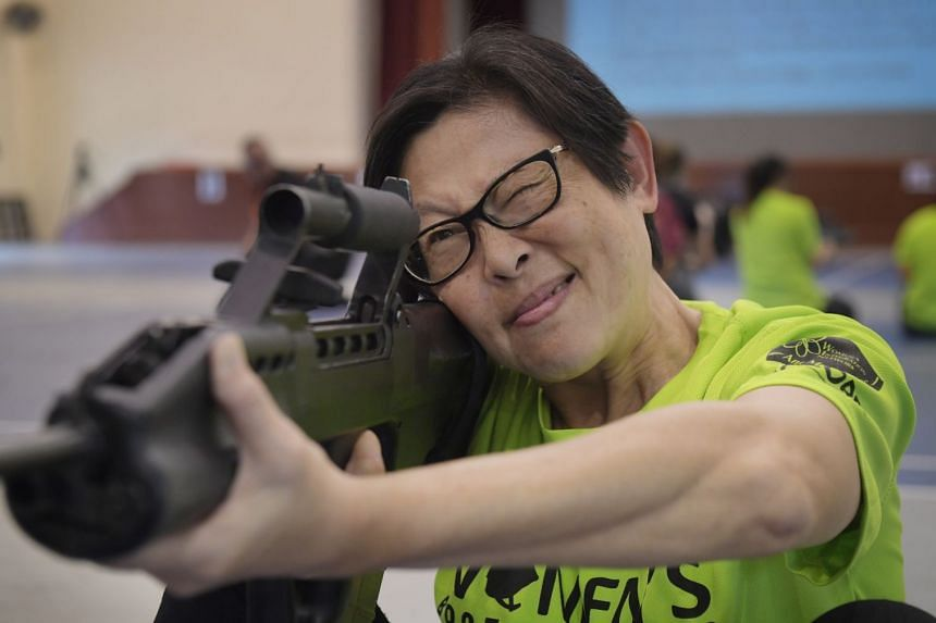 Madm Patsy Chong, one of the oldest participants in the Women's Boot Camp 2018 at 61 years old, practises aiming through the scope of a SAR21 rifle at Maju camp, on Sept 1, 2018.