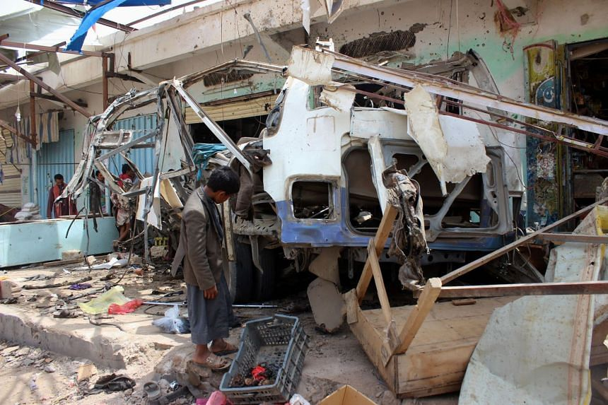 A Yemeni child stands next to a bus destroyed at the site of a Saudi-led coalition air strike.