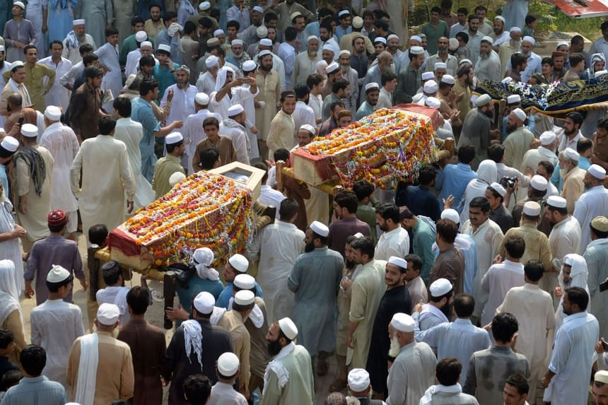 Pakistani residents carry the coffins of people killed in an election rally blast claimed by Taleban militants in July 2018.