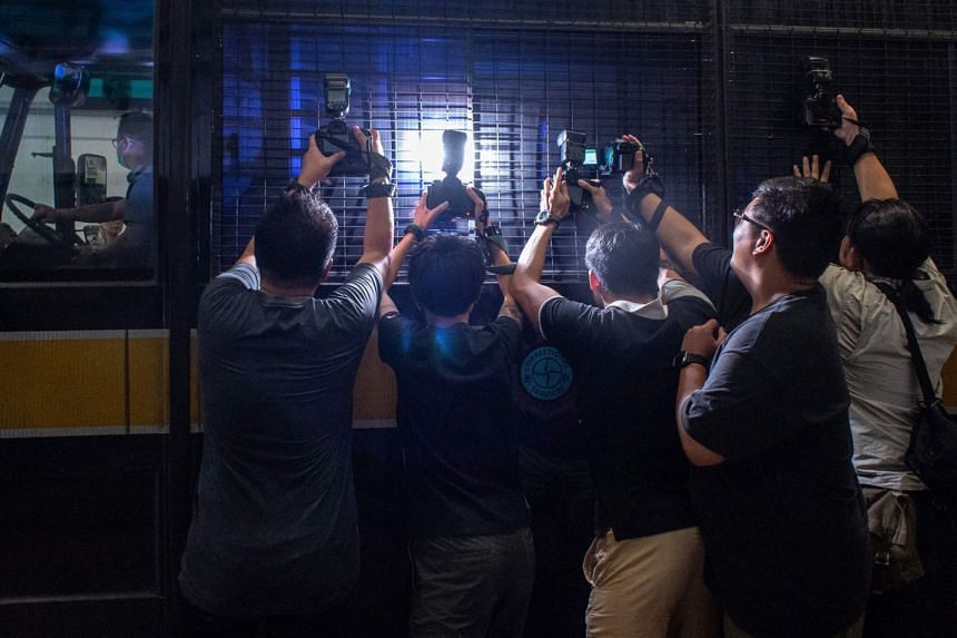 Photojournalists trying to get a picture of University of Hong Kong professor Cheung Kie Chung as he was transported in a prison van from a court in Hong Kong last Thursday.