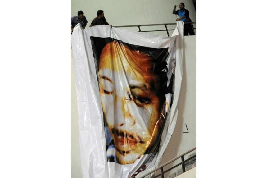 Supporters of Anwar Ibrahim hanging a poster of him at a rally in Selangor state on July 1, 2008, showing a black eye inflicted in a severe beating by former Malaysian police chief Abdul Rahim Noor.