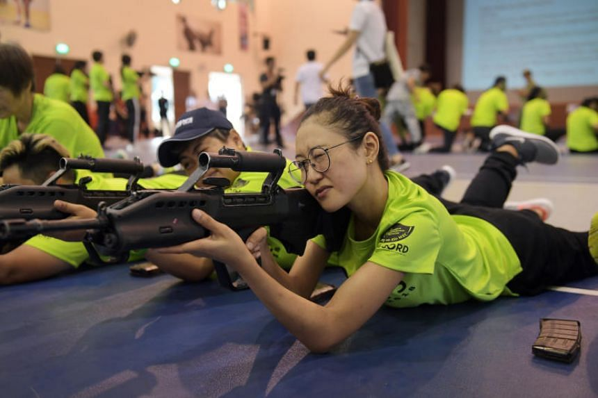 A participant practises aiming with a SAR21 rifle.