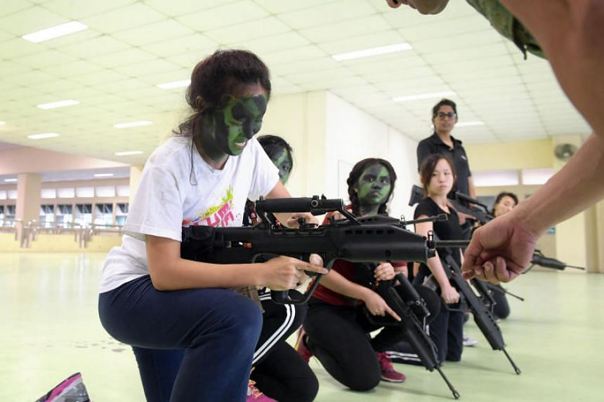 TNP journalist Adeline Tan, 23, learns how to operate a SAR21 rifle.