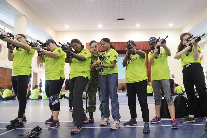 Participants practise aiming through the scope of a SAR21 rifle.