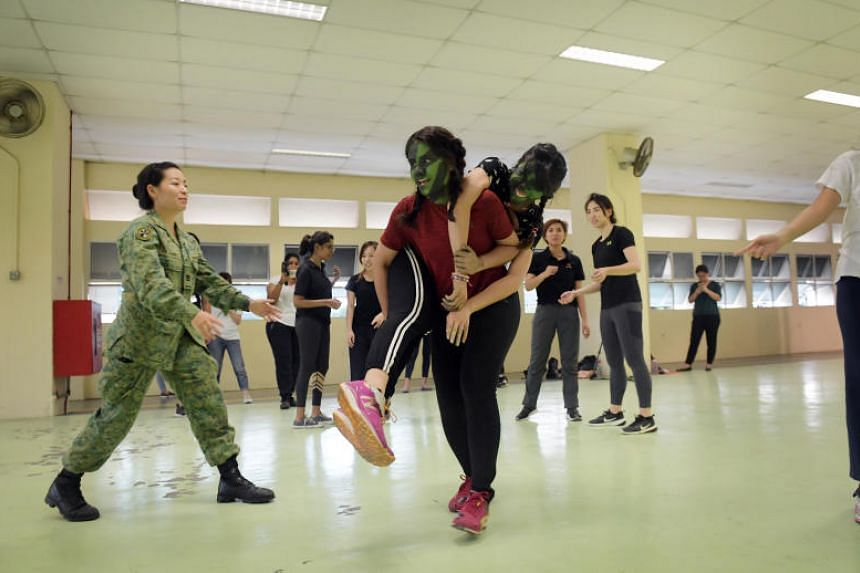 Journalist Farzanah Friday (in red) practises the fireman lift, a way of evacuating a casualty, with fellow journalist Bridget Tan.