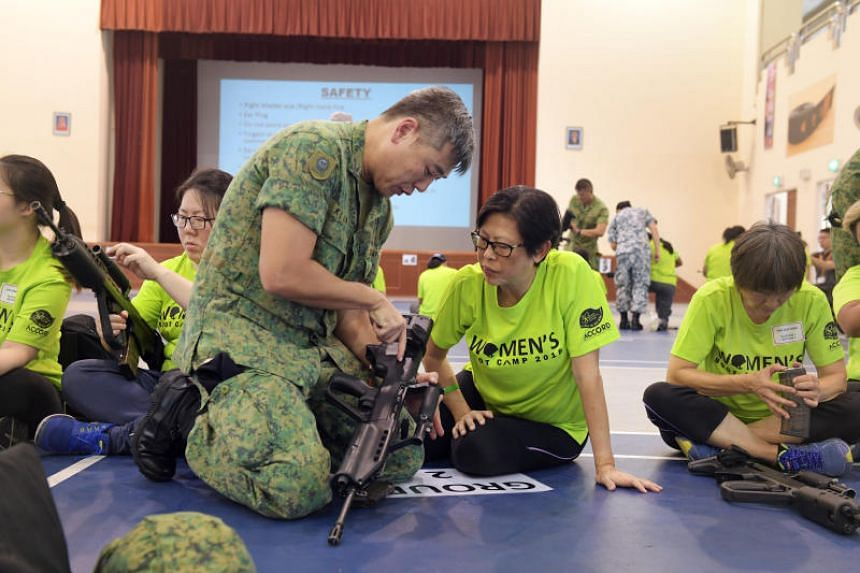 Madam Patsy Chong learning how to operate a SAR21 rifle.