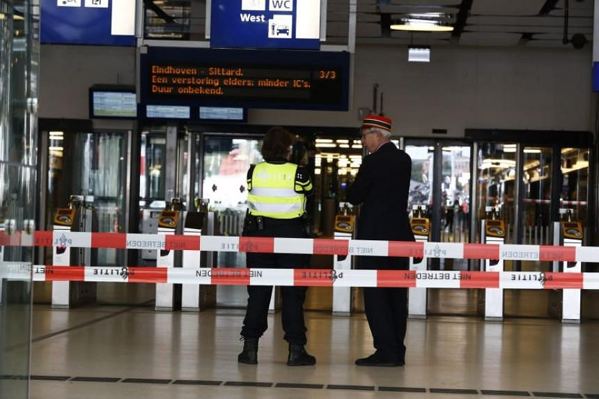 Officials stand inside a cordoned-off area at The Central Railway Station in Amsterdam on Aug 31, 2018, after two people were injured in a stabbing incident.