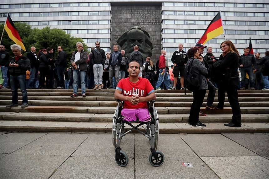 "An Iraqi man in a wheelchair wearing a ""No Nazi"" T-shirt in protest against a gathering of right-wing supporters in Chemnitz, Germany, on Saturday."