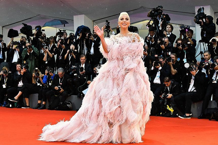 After playing a girl-next-door in A Star Is Born, Lady Gaga reverted to her flamboyant self, wearing a dress made of long pink feathers at the film's world premiere at the Venice Film Festival.