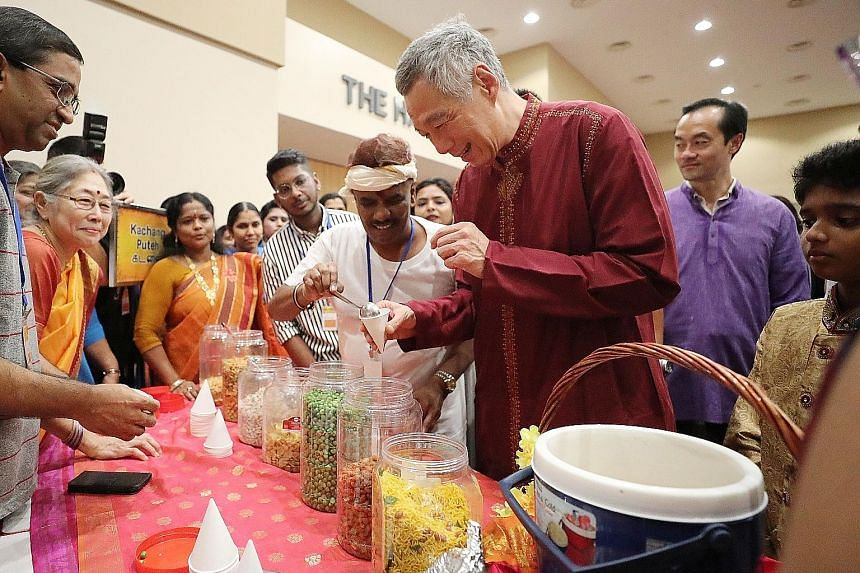 Prime Minister Lee Hsien Loong gets kacang putih, a traditional snack, from a stall at the Rhythms In Unity - Sangamam 2018 event, held at the Institute of Technical Education College Central campus. Behind him is Senior Minister of State for Trade a