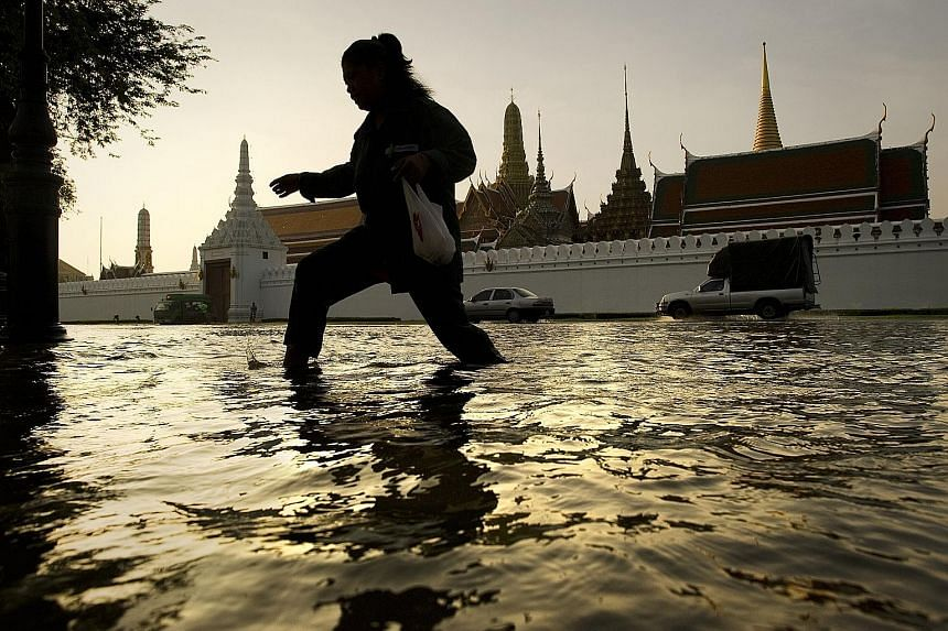 A woman wading through flood waters in front of the Grand Palace in Bangkok in 2011, when the monsoon season brought the worst floods in decades. Below: A drainage canal used for flood mitigation in Bangkok. It connects to a 6.4km underground tunnel
