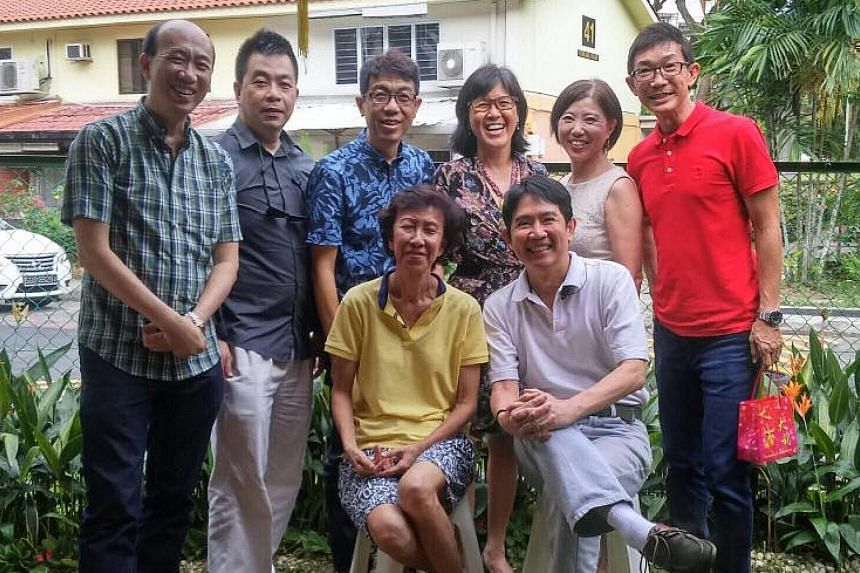 Mr Raymond Tan (standing, second from left) and six other former pupils of Delta West School with their teacher Tan Siam Tiam (seated) at her Stirling Road home during Chinese New Year in 2016.