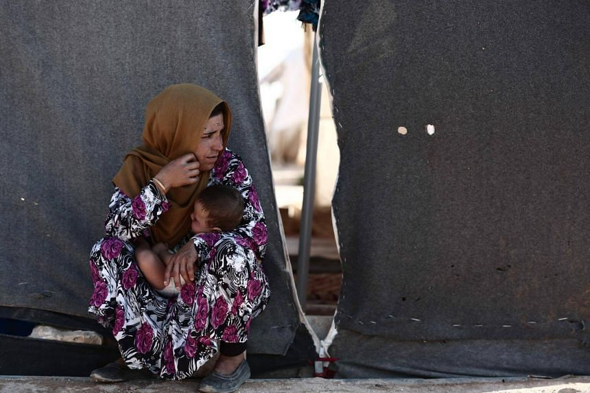 A woman carries a child as she sits in front of a tent at a camp for the displaced from the rebel-held Syrian province of Idlib, at the village of al-Ghadfa, on Sept 2, 2018.