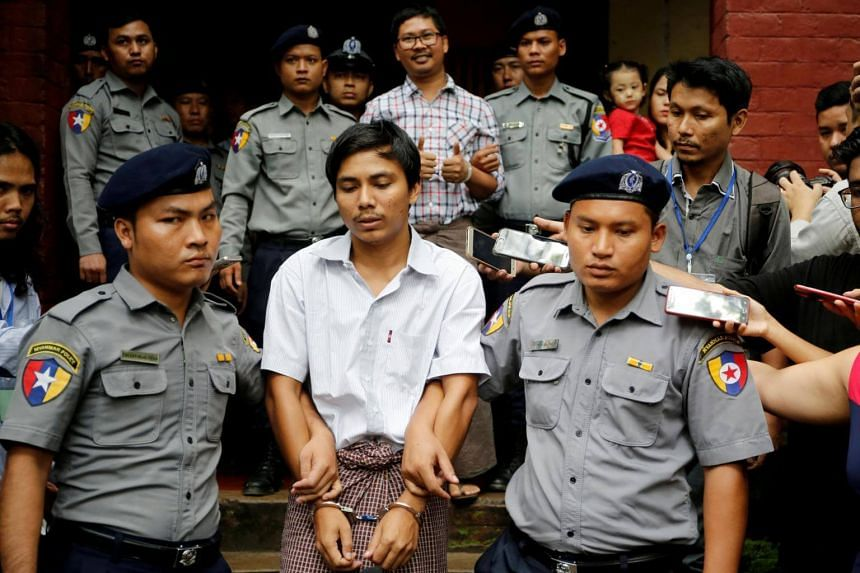 A file photo of detained Reuters journalist Kyaw Soe Oo (bottom, centre) and Wa Lone (top, centre) being escorted by police as they leave after a court hearing in Yangon, on Aug 20, 2018.