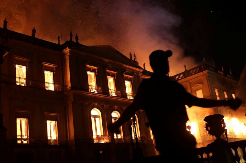 A policeman clears the area during a fire at the National Museum of Brazil in Rio de Janeiro, Brazil, on Sept 2, 2018.