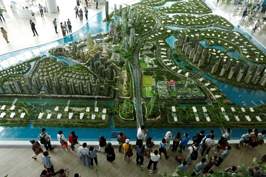 Prospective buyers look at a model of the development at the Country Gardens' Forest City showroom in Johor Baru, Malaysia, on Feb 21, 2017.