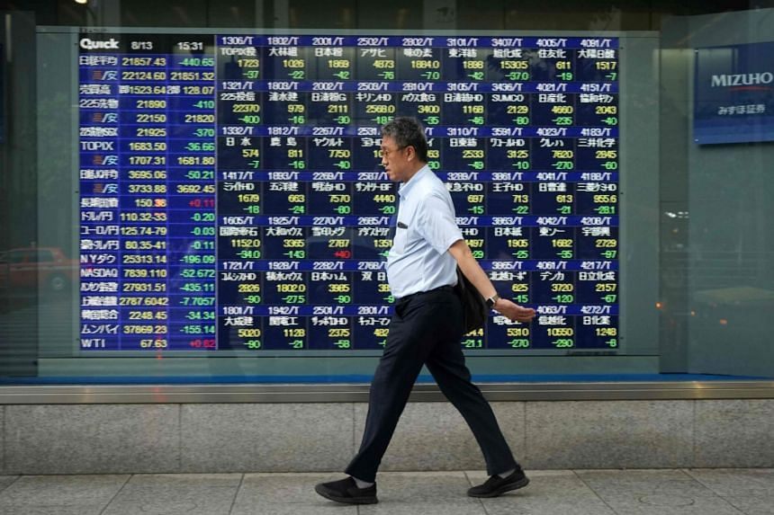 A pedestrian walks past a stock indicator board for the Tokyo Stock Exchange in Tokyo, on Aug 13, 2018.