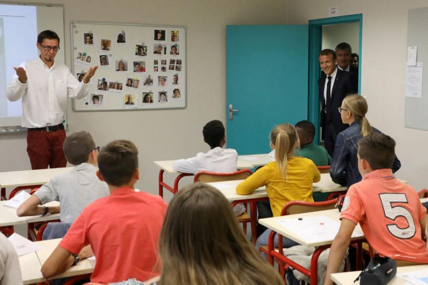 French President Emmanuel Macron enters a classroom during a visit in a secondary school in Laval, France, on Sept 3, 2018.