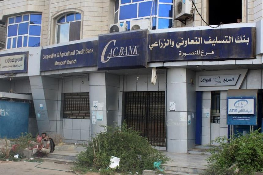 A Yemeni man sits by a closed bank and other shops due to a protest in Aden, on Sept 3, 2018.