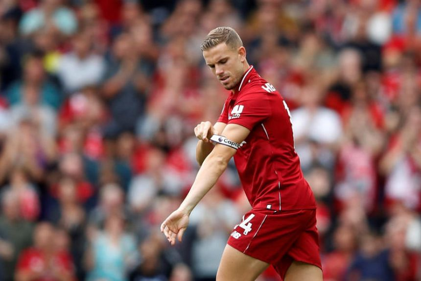 Liverpool's Jordan Henderson puts on the captain's armband after coming on as a substitute at Anfield, Liverpool, Britain, on Aug 12, 2018.
