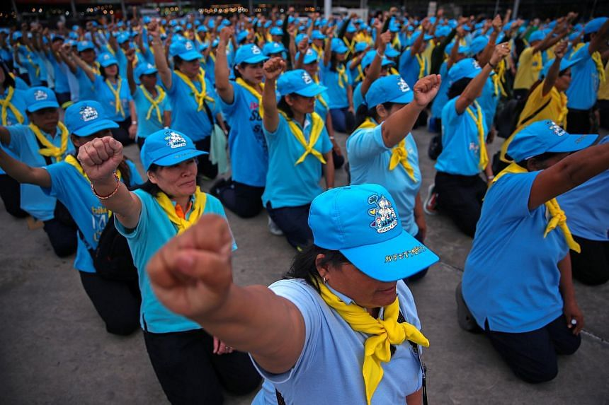 Volunteers of the Thai King in blue caps and yellow foulards shouting slogans before the start of a cleaning program at a market in Bangkok, Thailand, on Aug 8, 2018.