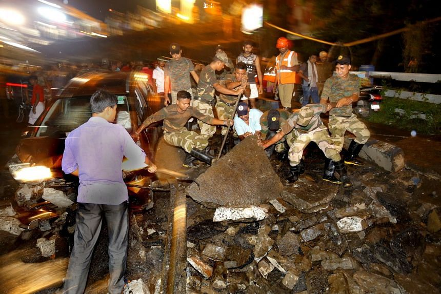 People gather while National Disaster Response Force and Indian army personnel work at the site of the collapsed bridge.