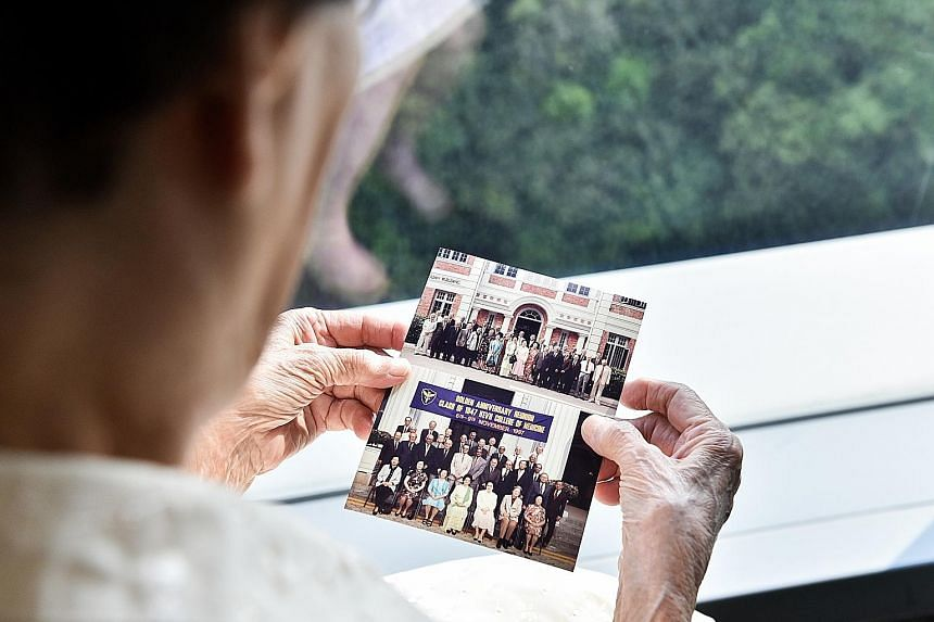 Dr Wong looking at photos of her classmates from King Edward VII College of Medicine. Her classmates included Malaysian Prime Minister Mahathir Mohamad and his wife Siti Hasmah Mohamad Ali.