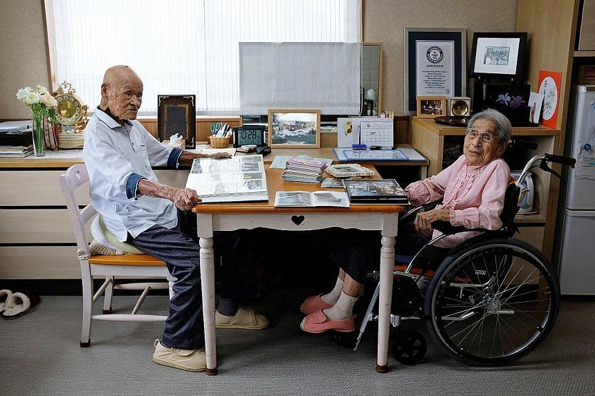 The world's oldest living married couple, Mr Masao Matsumoto and wife Miyako, with their family albums at the nursing home in Takamatsu, Japan, where they live.