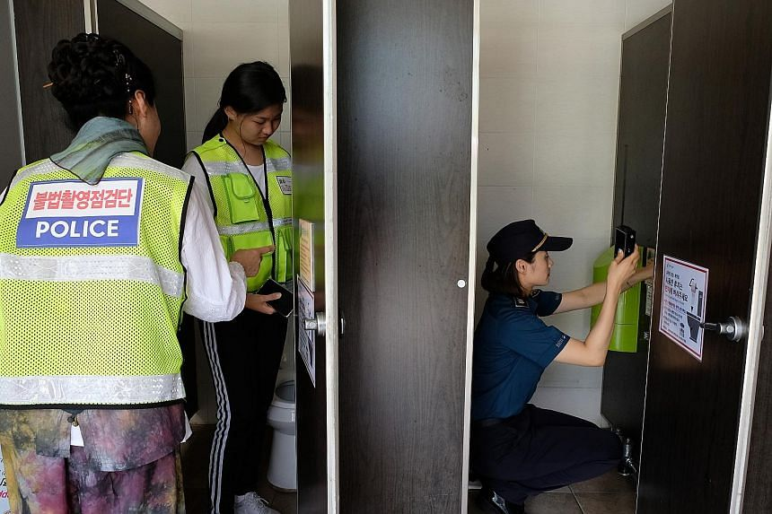 A spy-camera search squad inspecting a public toilet near a swimming pool in Changwon, South Korea.
