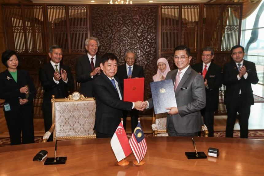 Coordinating Minister for Infrastructure and Minister for Transport Khaw Boon Wan (left) and Malaysian Economic Affairs Minister Azmin Ali inked the agreement at the Prime Minister's Office in Putrajaya on Sept 5, 2018.