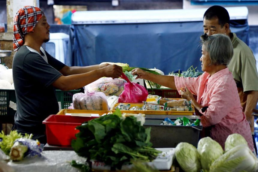 A customer pays for vegetables at a wet market in Klang, Malaysia, on October 27, 2017.