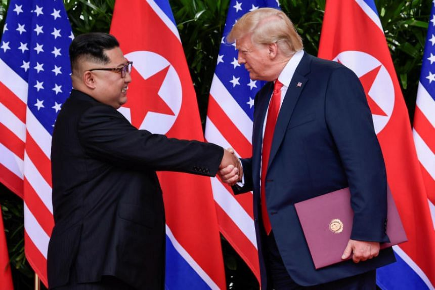 US President Donald Trump and North Korea's leader Kim Jong Un shake hands during the signing of a document after their summit at the Capella Hotel on Sentosa, on June 12, 2018.