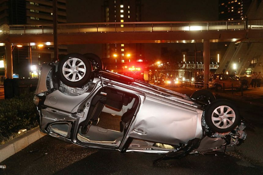 A car lies upside-down along a road after being blown by Typhoon Jebi's strong winds in Osaka.