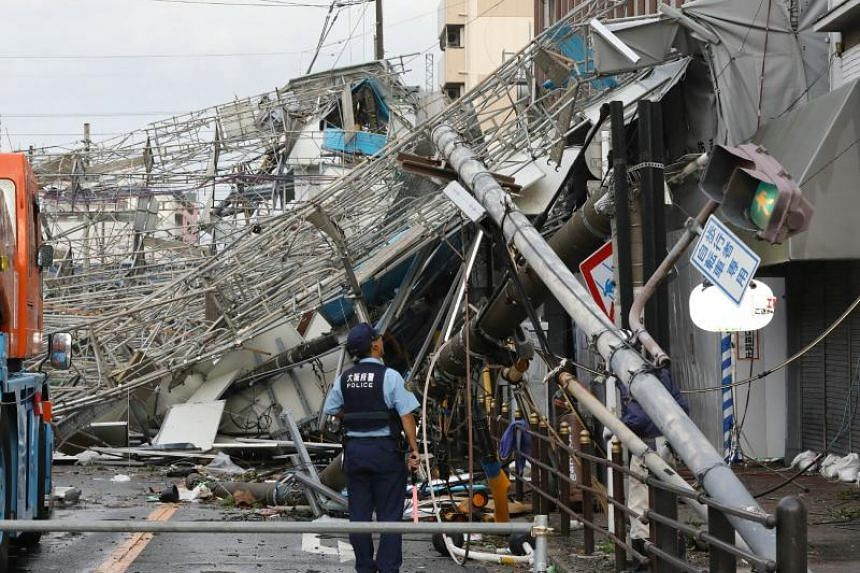 Damaged traffic boards and telecommunication relay poles are seen after they were brought down by strong winds caused by typhoon Jebi in Osaka on Sept 4, 2018. The strongest typhoon to hit Japan in 25 years made landfall on Sept 4, the country's weat