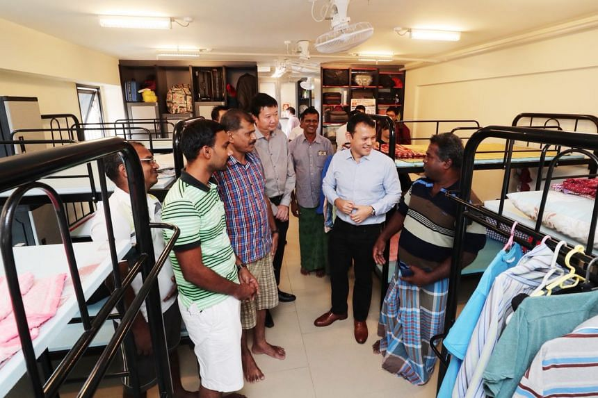 Minister of State for Manpower Zaqy Mohamad (second from right) talking to foreign workers in a dorm at Greyform Building.
