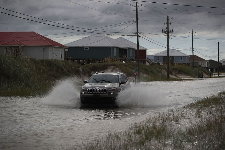 A vehicle drives along a flooded street caused by the approaching Tropical Storm Gordon in Dauphin Island, Alabama, on Sept 4, 2018.