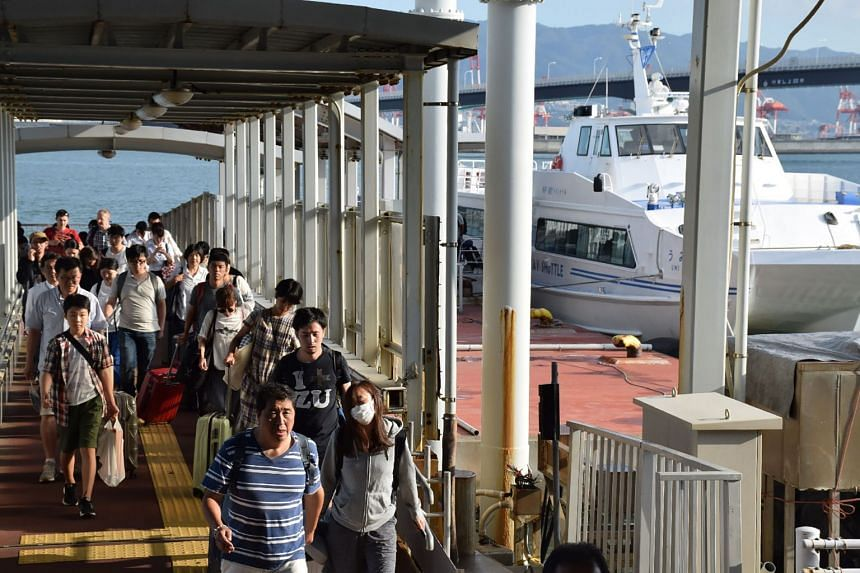 Passengers stranded overnight at the Kansai International Airport due to typhoon Jebi arrive at the Kobe port by boat on Sept 5, 2018.