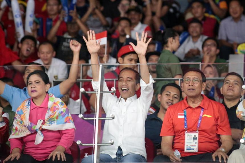 Indonesian President Joko Widodo (centre) reacts during the men's team finals badminton match between China and Indonesia at the 18th Asian Games in Jakarta, Indonesia, on Aug 22, 2018.