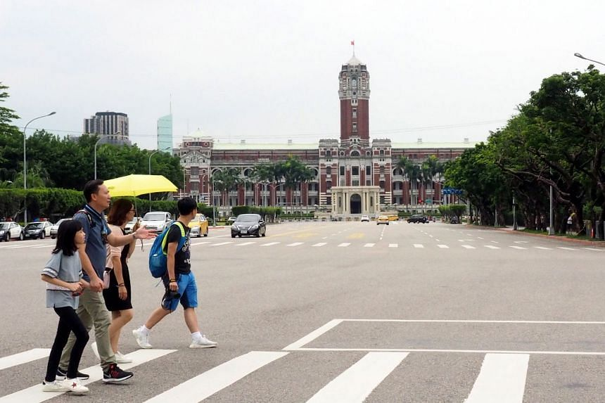 Tourists walk past Taiwan's Presidential Office Building in Taipei, Taiwan.