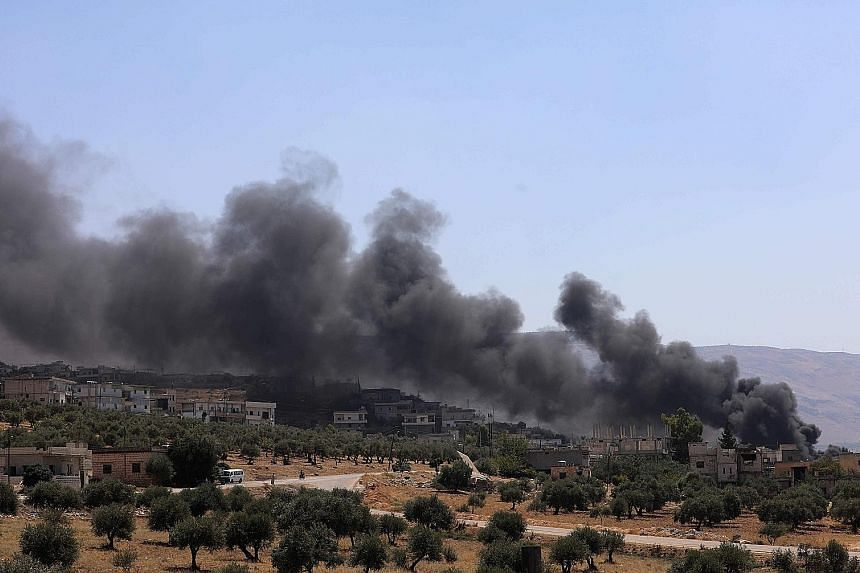 Smoke coming out of buildings that caught fire after being reportedly hit by Russian air strikes in the rebel-held town of Muhambal, about 30km south-west of Idlib.