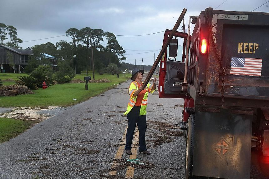 Mobile County government employee Wanda Williams cleaning up debris left behind by Tropical Storm Gordon yesterday as it passed through the area in Bayou La Batre, Alabama. Governors in Louisiana, Mississippi and Alabama declared a state of emergency