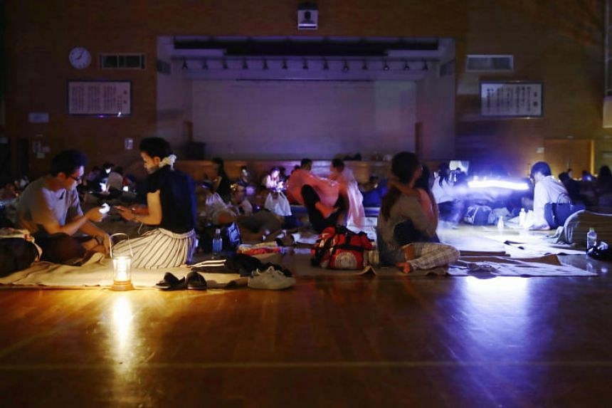 Evacuees are seen at a gymnasium of elementary school, acting as an evacuation shelter, during a blackout after an earthquake hit the area in Sapporo, Hokkaido, on Sept 6, 2018.