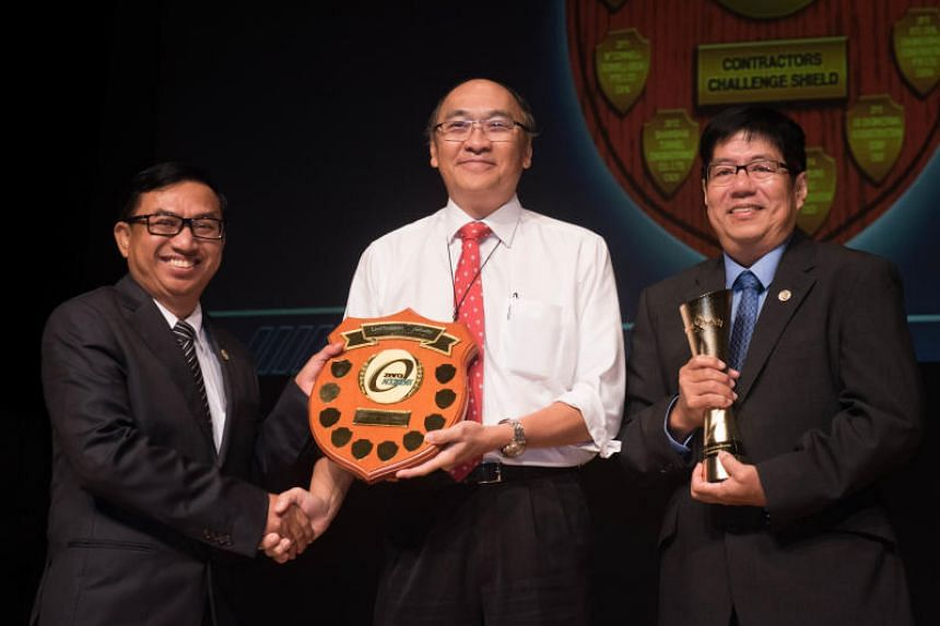 LTA chairman Alan Chan presenting the LTA Contractors Challenge Shield to Shanghai Tunnel Engineering Co (Singapore)'s workplace safety and health manager Thant Zaw (left) and managing director Khor Eng Leong.