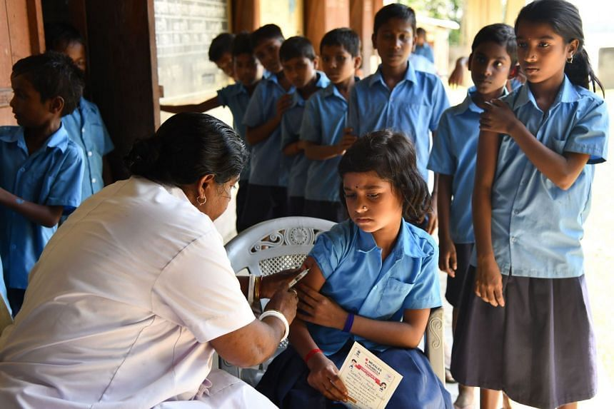 An India health worker injects a measles and rubella (MR) vaccine to a student at a government school at Hatibhangi village in Morigoan in Assam state on Sept 4, 2018.
