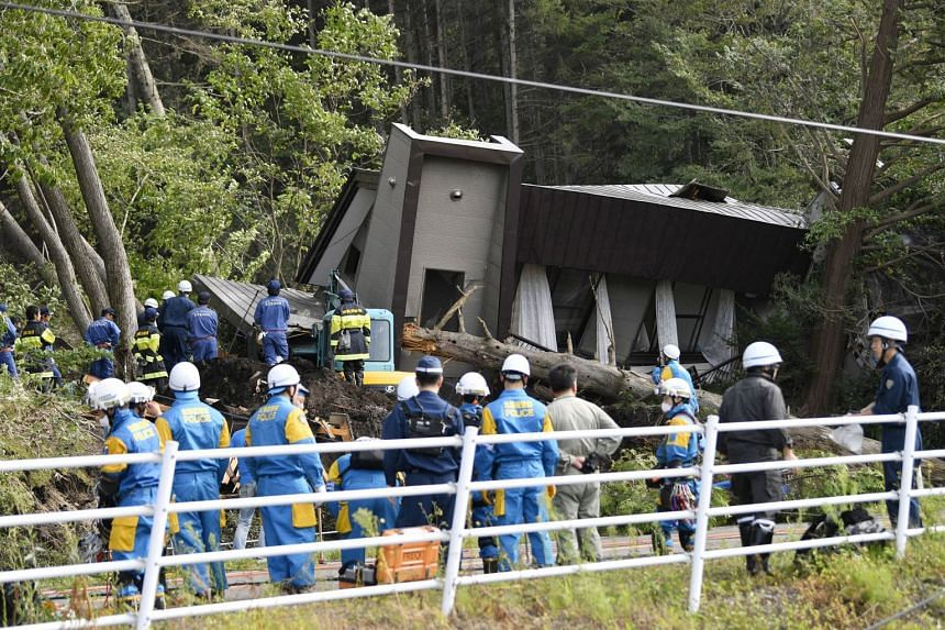 Police and rescue workers search for survivors from a house that was damaged by a landslide caused by an earthquake in Atsuma town in Hokkaido prefecture, on Sept 6, 2018.