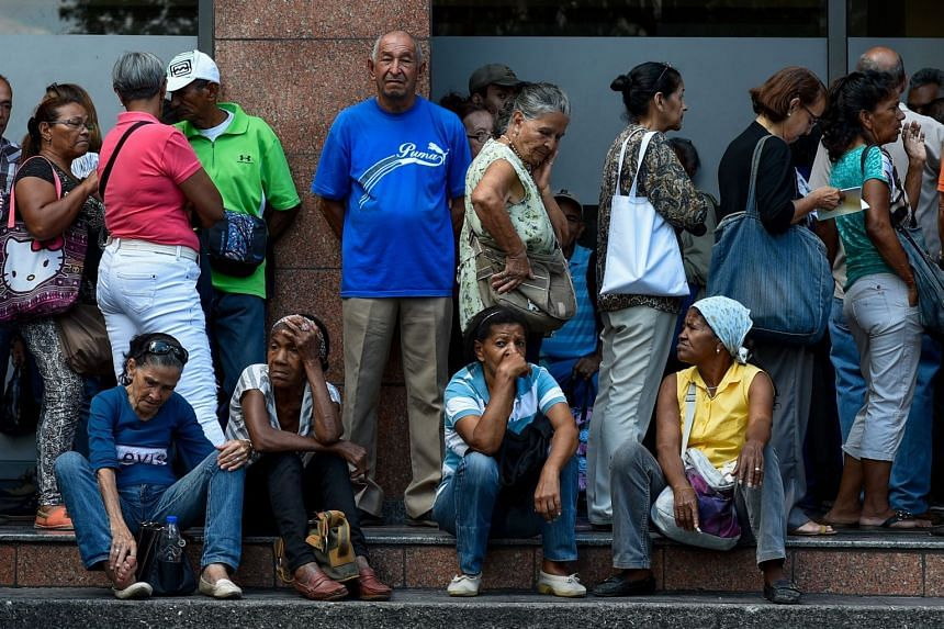 People line up to withdraw part of their pensions outside a bank branch in Caracas on, Sept 3, 2018.