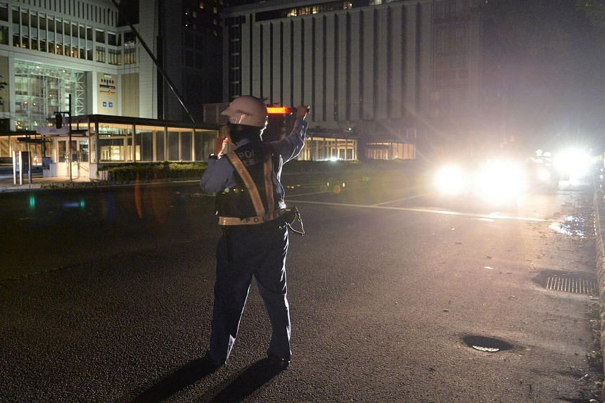 A police officer stands at a crossing following a blackout after a strong earthquake hit during the night in Sapporo, northern Japan, on Sept 6, 2018.