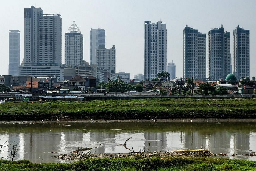 Buildings of the Jakarta skyline are seen past shantyhouses on, July 4, 2017.