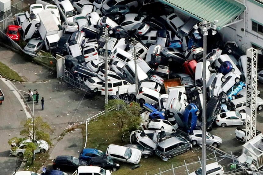 Vehicles damaged by heavy winds brought on by Typhoon Jebi in Kobe, western Japan. Some roads and train lines in the affected areas remained closed yesterday.